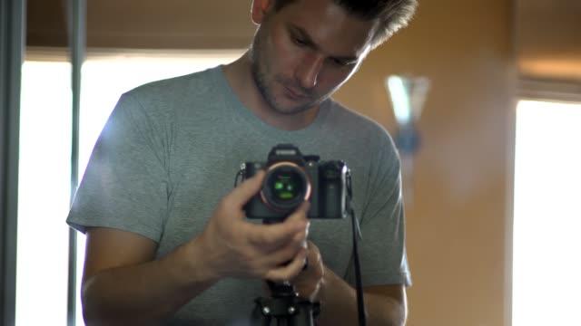 young photographer or videographer adjusts his camera - pochodzenia rosyjskiego filmów i materiałów b-roll