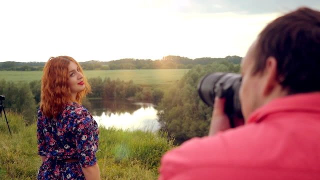 Young photographer takes photo of young red-haired woman at summer outdoor on nature