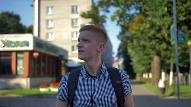 Young photographer with photo camera walks around the small european town