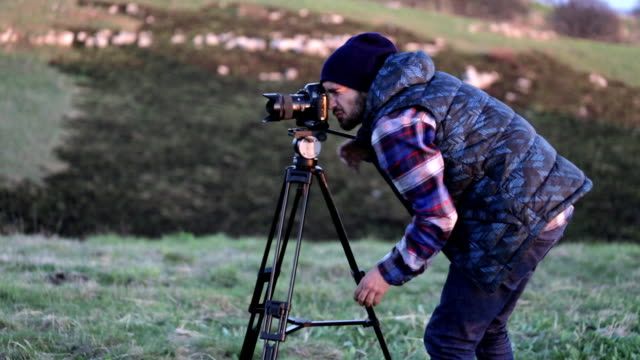 Young photographer working in the nature with camera and tripod video