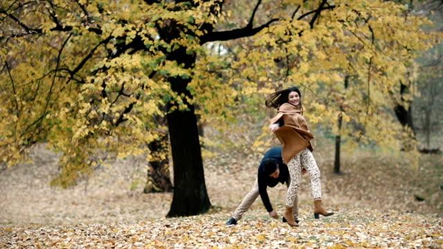 stockvideo's en b-roll-footage met jonge speelse paar plezier terwijl het achtervolgen in herfstdag in het forest. slow-motion. - s