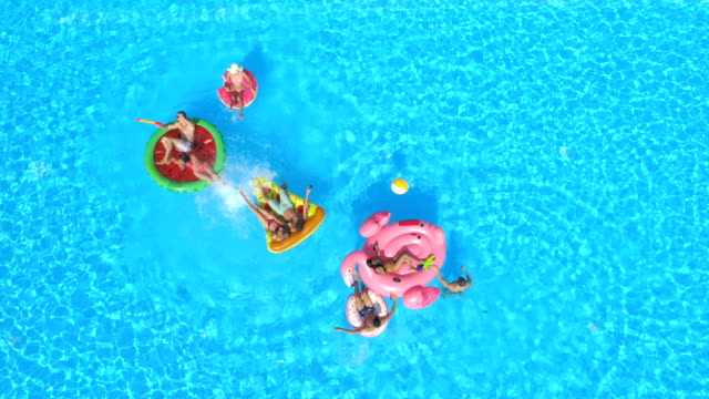 AERIAL: Young playful people having fun on inflatable colorful floaties in pool AERIAL: Cheerful friends having water fight on colorful floaties at pool party. Playful guys and girls splashing water and taking selfies on inflatable pizza, doughnut, flamingo and watermelon floats pool party stock videos & royalty-free footage