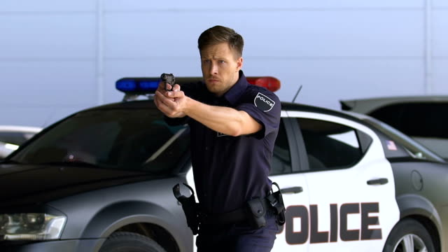 Young police officer aiming gun, detaining criminal outdoors, district security