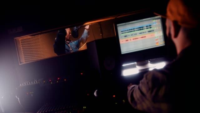 vídeos de stock e filmes b-roll de young pop star and music producer recording song at studio - compositor