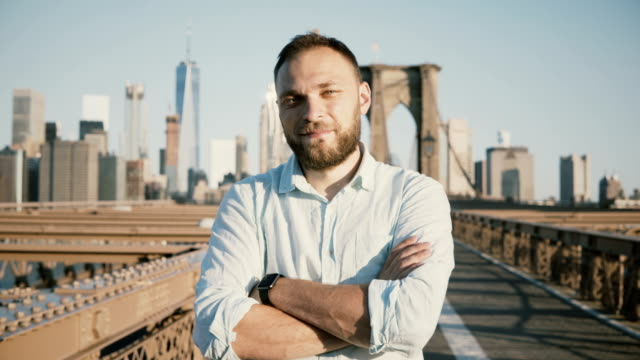 vídeos de stock e filmes b-roll de young positive male caucasian businessman with arms crossed looking at camera, smiling at brooklyn bridge, new york 4k - braço