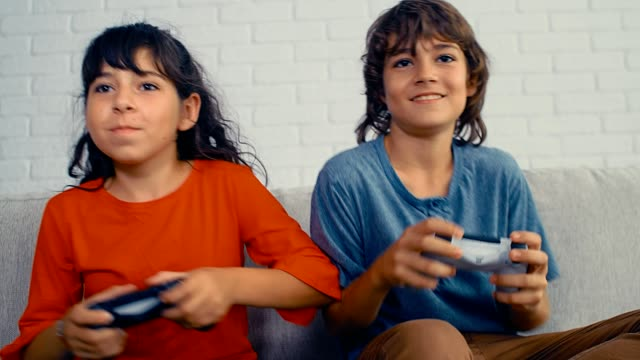 Young pre teenage boy and girl playing video game console, have fun, laugh, hold the joystick, celebrating victory, 4k