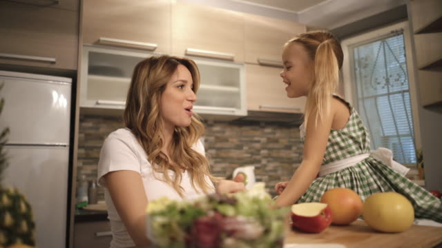 Young pregnant mother and her small daughter eating a healthy snack in the kitchen and talking. Cute little girl feeding her pregnant mother with an apple while enjoying in the kitchen and talking to each other. tasting stock videos & royalty-free footage