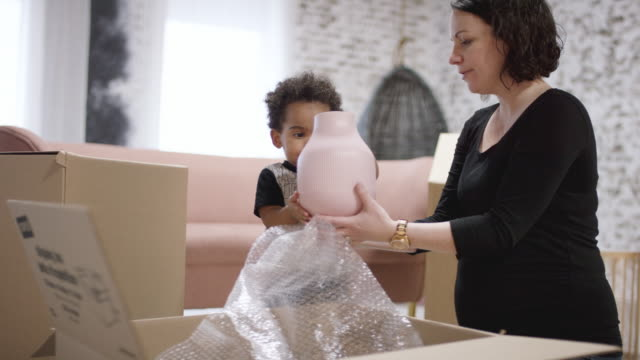 Young Pregnant Mother Unpacking With The Help Of Her Toddler Son