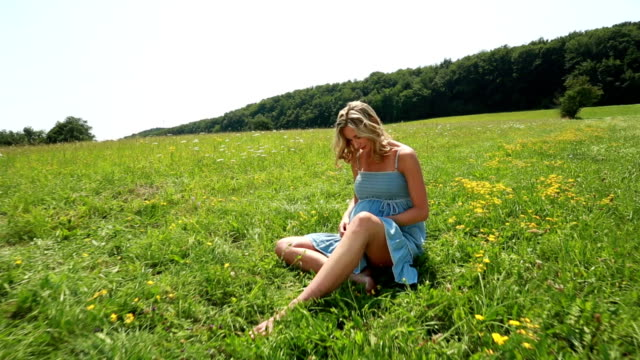 young pregnant woman enjoying summer day in meadow video