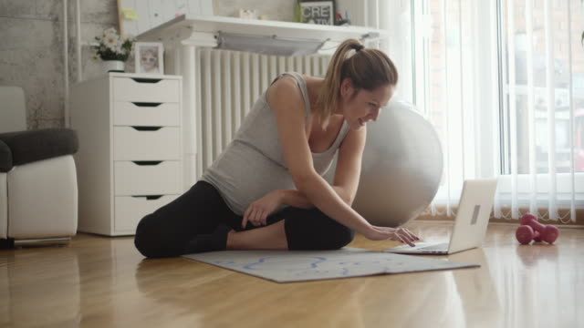 young pregnant woman exercises at home. - tappetino video stock e b–roll