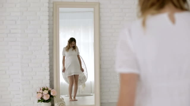 Young pregnant woman in a white dress having fun dancing in front of a mirror. Young pregnant woman in a white dress having fun dancing in front of a mirror. Positive beautiful expectant mother moving in front of the mirror in the studio. dress stock videos & royalty-free footage