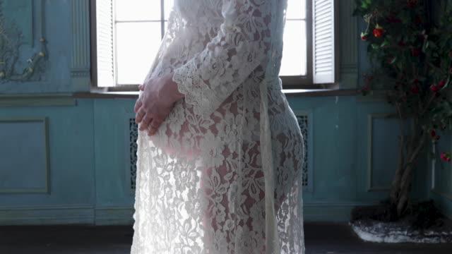 ung gravid kvinna i transparent klänning strök hennes mage - aftonklänning bildbanksvideor och videomaterial från bakom kulisserna