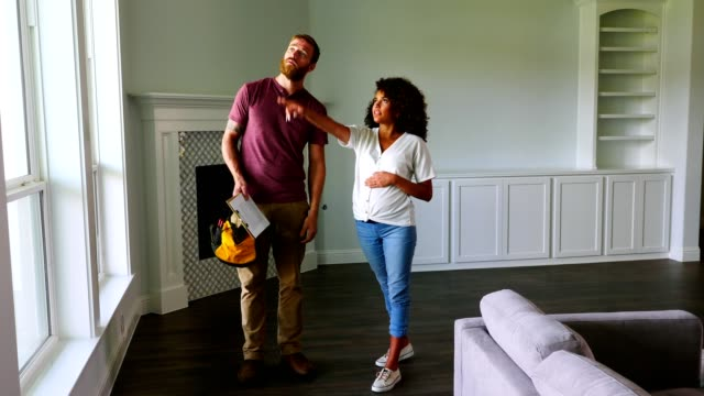 young pregnant woman talks with contractor in new home - imprenditore edile video stock e b–roll