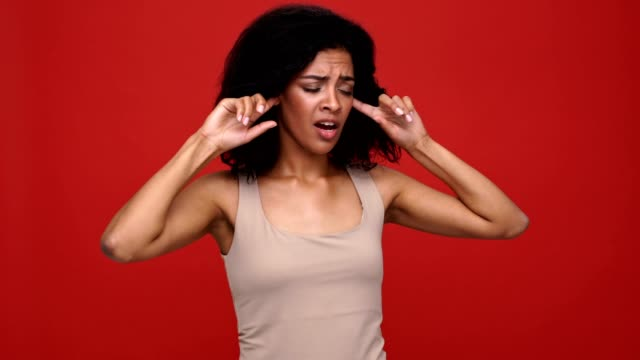 Young pretty african woman covering ears don't want to hear you over red background. video