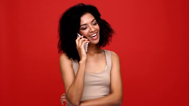 Young pretty african woman smiling talking by phone over red background. video