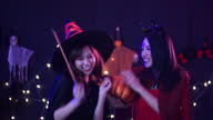 istock Young pretty Asian women wearing witch costume at the Halloween party with black background and decoration light 1278285013