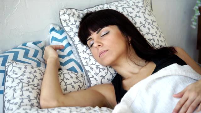 かなりブルネットの若い女性は日当たりの良い朝、彼女のベッドで眠っているクローズ アップ - チャームポイント点の映像素材/bロール