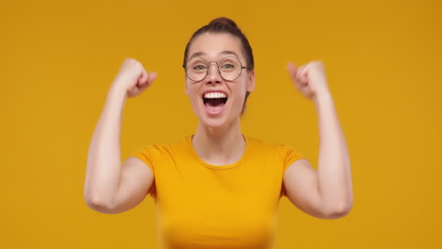 Young pretty fan girl shouting while her team win, raised both fists in victory gesture, isolated on studio yellow background