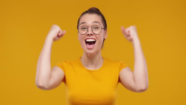 giovane bella fan girl che gridava mentre la sua squadra vinceva, alzò entrambi i pugni nel gesto della vittoria, isolata su sfondo giallo studio - pugno video stock e b–roll