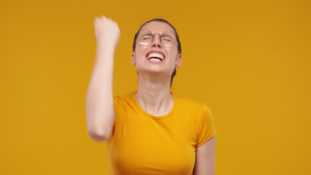 Young pretty fan girl shouting while her team wins, raised fist in victory gesture, isolated on studio yellow background