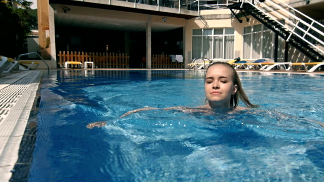 Young pretty fashion sport woman posing outdoor in summer on tropic island in hot weather in bikini on pool. Outdoors lifestyle portrait video