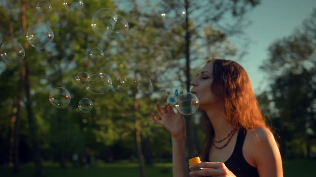 Young pretty female making soap bubbles. Beautiful tree with orange leaves video