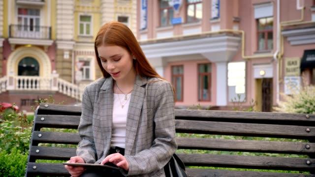 stockvideo's en b-roll-footage met jonge gember vrij vrouw in jas zittend op de bank en het gebruik van tablet pc, stad straat achtergrond - men blazer