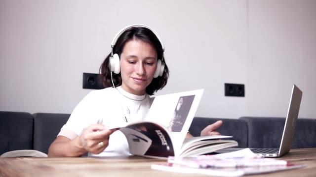 stockvideo's en b-roll-footage met mooi meisje geniet van haar tijd terwijl u door, het lezen van het tijdschrift. zit door de tabel en luistert naar de muziek in de koptelefoon. ontspannen. binnenshuis - woman home magazine
