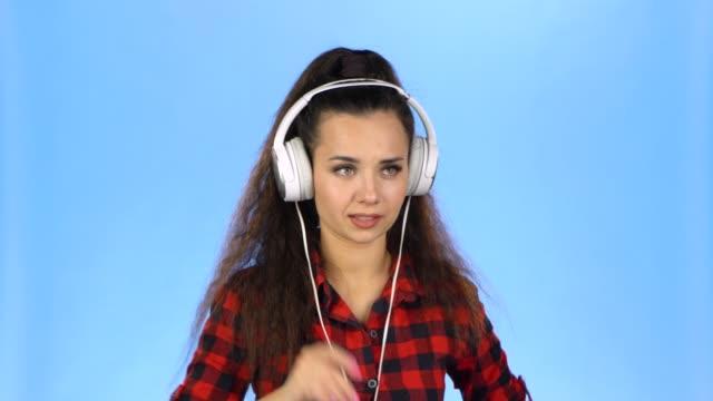 stockvideo's en b-roll-footage met jong mooi meisje luisteren verschillende liedjes in hoofdtelefoon - paardenstaart haar naar achteren