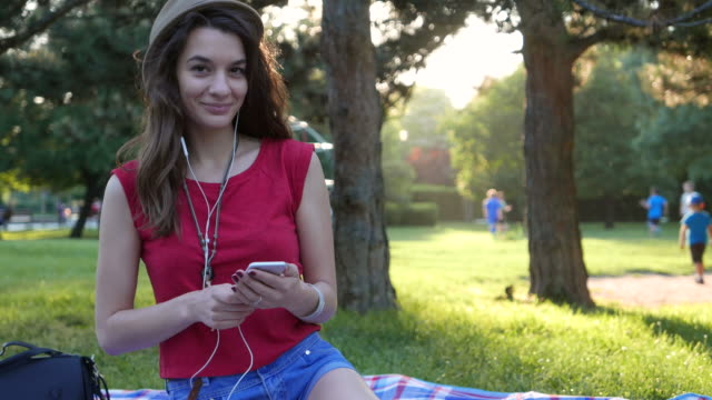 Young pretty girl listening to music in the park