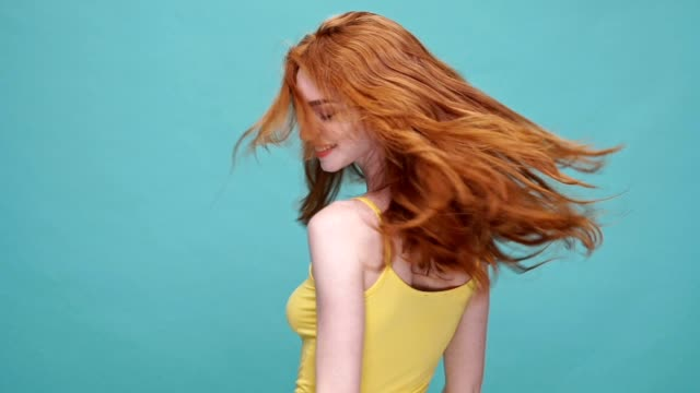 Young pretty girl with long red hair shaking her head isolated over blue background