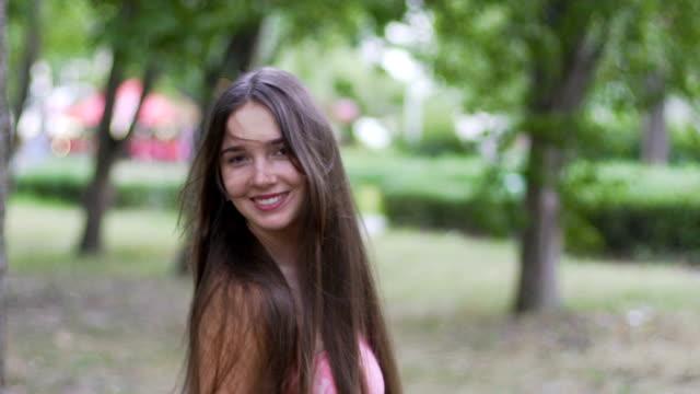 young pretty lady turns around flips hair smiling beautiful woman joyful outdoor - brązowe włosy filmów i materiałów b-roll