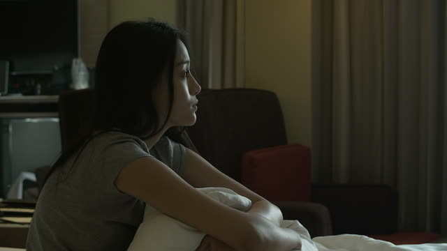 4K: Young pretty lonely sad girl sitting on sofa and hugging her knees video