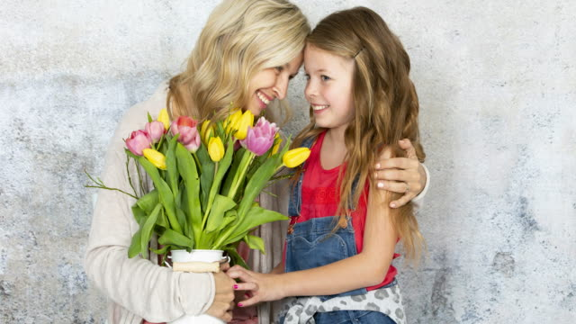 Young pretty mother gets a bouquet of colorful flowers from her daughter on Mother's Day video