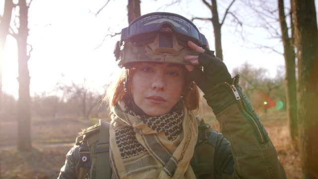 young pretty redhead woman in military uniform armed with rifle at the battlefield area - armia filmów i materiałów b-roll