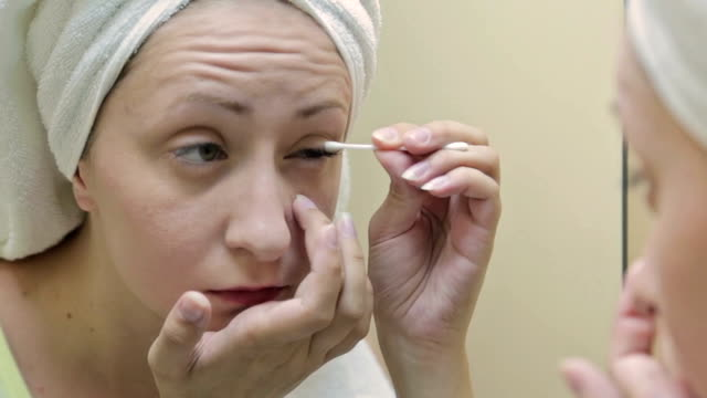 Young, pretty woman applying concealer on her eyelid in bathroom video