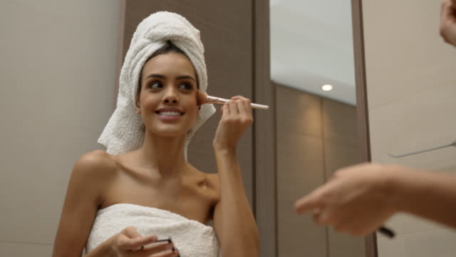 Young pretty woman applying make up looking at mirror cheerfully Young pretty woman applying make up looking at mirror cheerfully during her morning routine wearing a towel stock videos & royalty-free footage