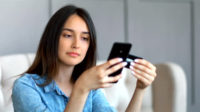 Young pretty woman buying online with credit card and smartphone sitting on a couch in the living room at home video