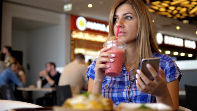 Young Pretty Woman Drinks Juice From the Tube to the Cafe, Using a Smartphone video