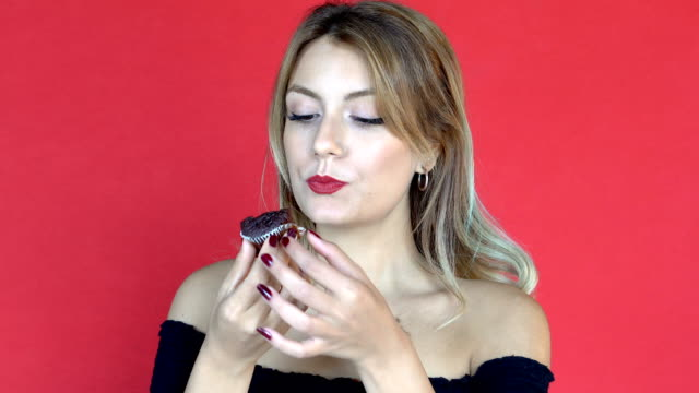 Young pretty woman eating muffin against red background. FacialExpressions