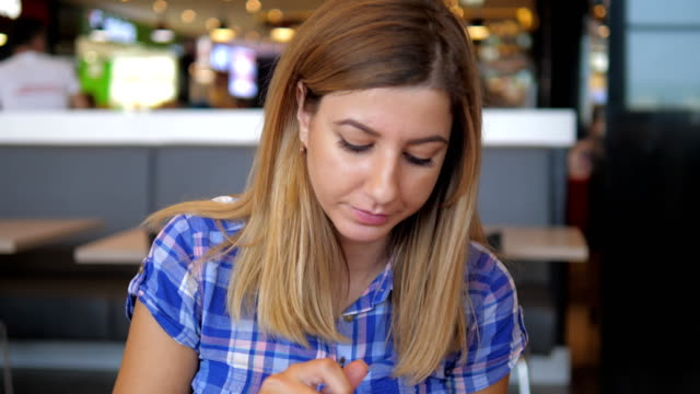 Young Pretty Woman In Blue Shirt In Cage Eats At Cafe video