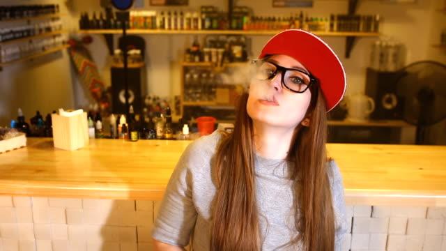 genç kadın kırmızı bere duman elektronik sigara vape dükkanında güzel. portre - nikotin stok videoları ve detay görüntü çekimi