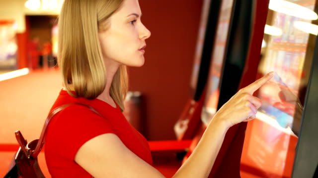 Young pretty woman in red t-shirt buying movie ticket from vending machine at cinema video