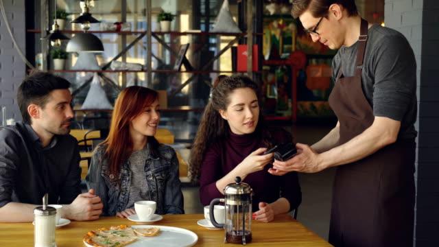 vídeos de stock, filmes e b-roll de jovem mulher bonita está pagando com smartphone refeição no café depois do almoço com os amigos. tecnologia moderna, pagamento sem contacto e comer fora do conceito. - pagando
