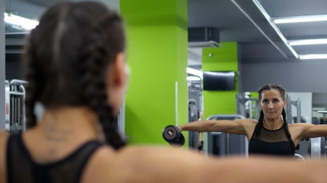 la giovane bella donna si allena in palestra sollevando e abbassando i manubri davanti allo specchio. palestra sportiva che si allena con i pesi e lavora sulle muscolate. da vicino. stile di vita attivo sano - dorso umano video stock e b–roll