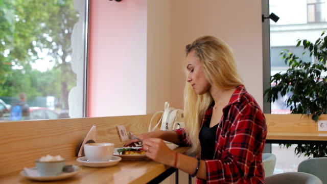 Young pretty woman with smartphone in cafe video