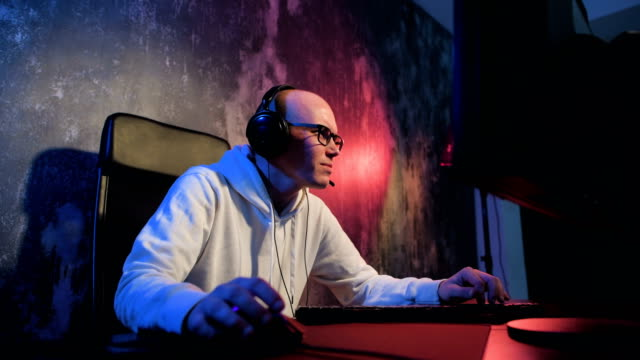 young pro gamer playing in online video game, talks with team players through microphone. neon colored room. e-sport cyber games internet championship - atleta professionista video stock e b–roll