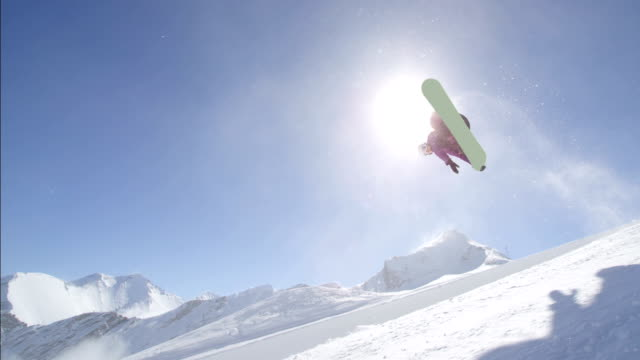 SLOW MOTION: Young pro snowboarder jumping over the sun in half pipe snow park video