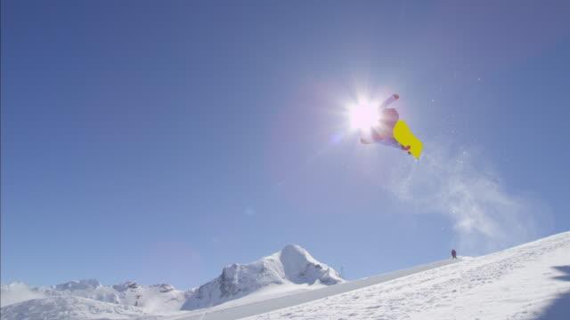 slowmotion: unga pro snowboarder hoppa över solen i halfpipe snowpark - vintersport bildbanksvideor och videomaterial från bakom kulisserna