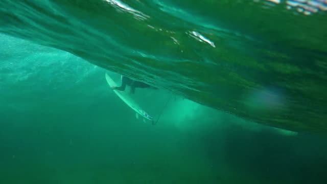 SLOW MOTION UNDERWATER: Young pro surfer girl doing duck dive